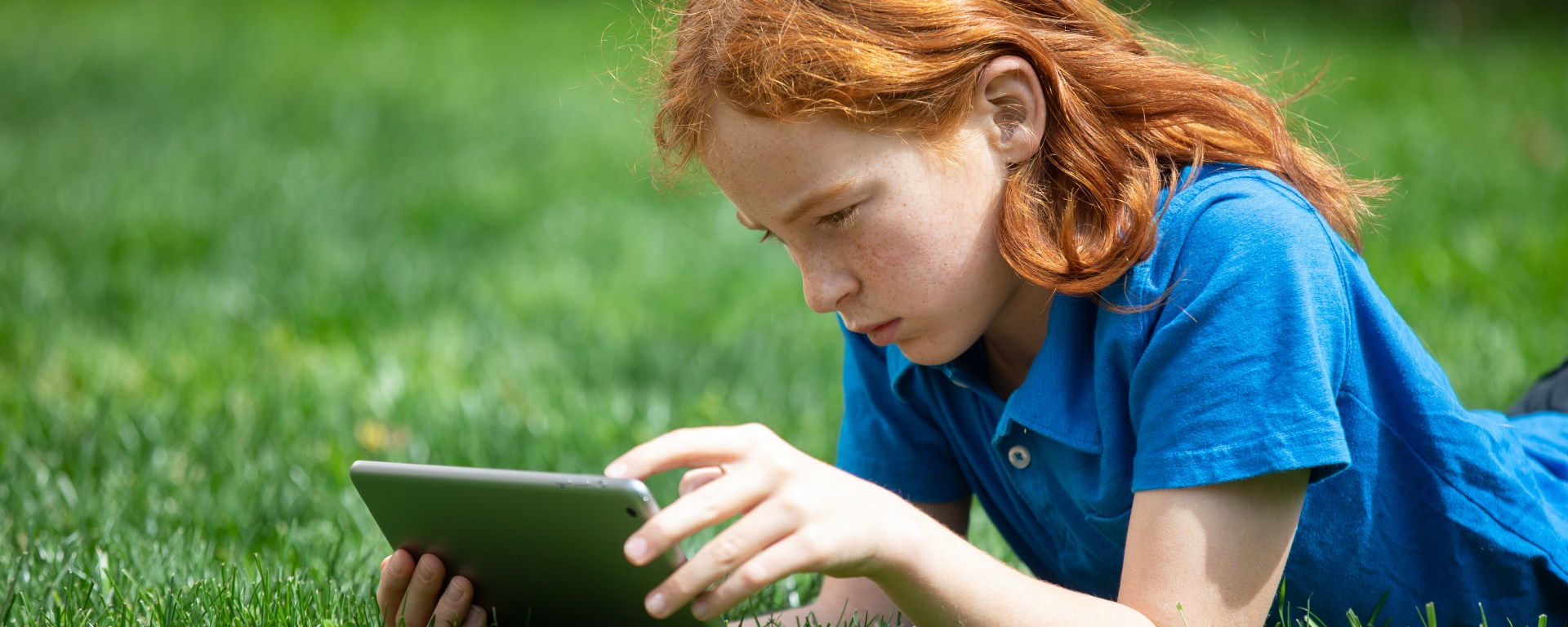 Student lays in grass on iPad