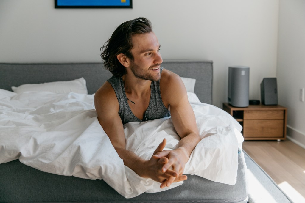 man sitting and smiling in bed