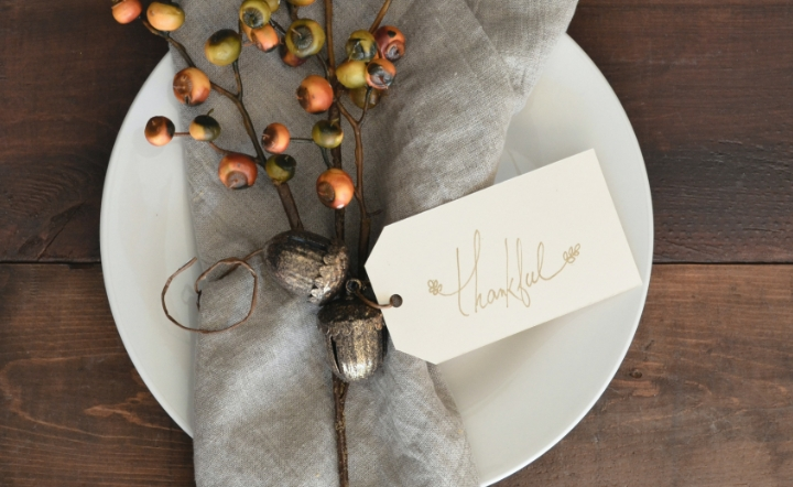 Gray napkin with name card on white plate on wooden dining table
