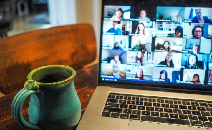 Mug with black and silver MacBook Pro displaying a group of people on Zoom app