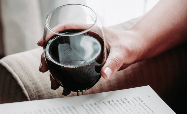 Person holding wine glass reading book