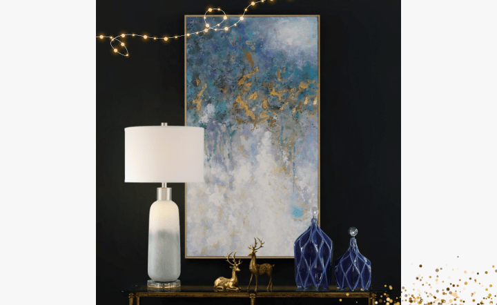 Gray and white table lamp, blue bottles, gold deer, and multicolor wall art in lifestyle setting