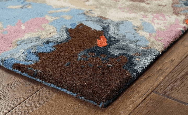 Close up of multicolor area rug on wood floor