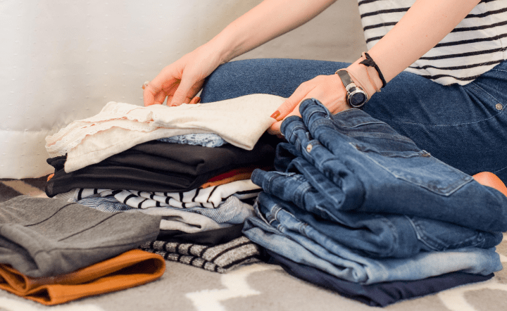 Close up of woman in striped shirt organizing piles of clothes