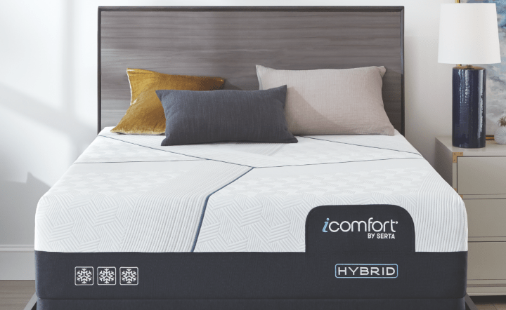 Serta hybrid mattress with gray bed frame and dark blue lamp in lifestyle setting