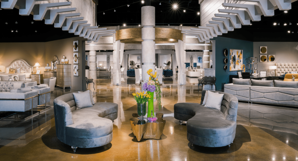 Gray Living Room sofas and stainless steel coffee table with flower arrangements in a showroom setting by El Dorado Furniture.