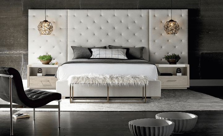 Rug, ceiling lamps, cream bed, bench, and nightstands in lifestyle setting