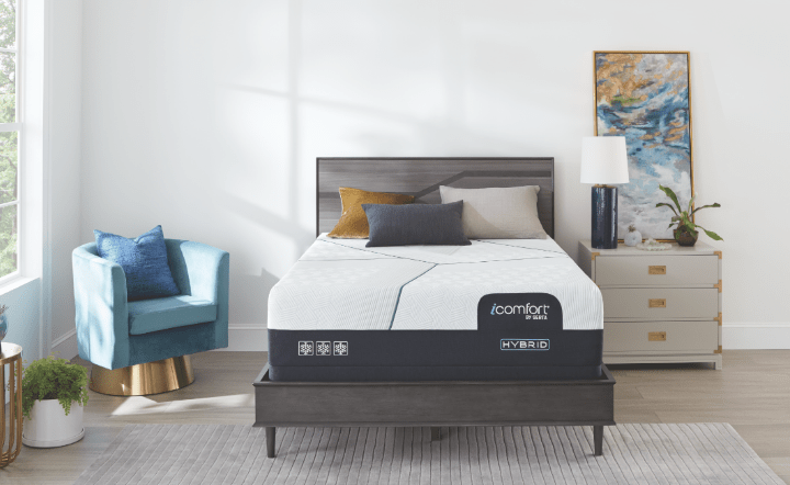 Serta mattress on gray bed frame with nightstand, blue chair, gold table, plants, and wall art in lifestyle setting