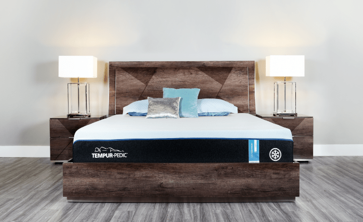 Tempur-pedic mattress on brown bed frame with brown nightstands and table lamps in lifestyle setting