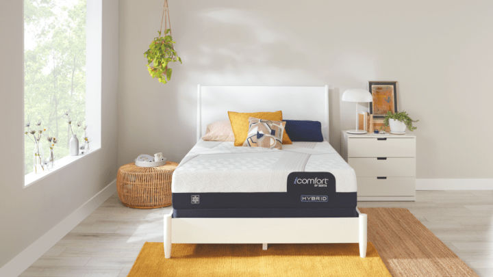 Mattress on white bed with white nightstand and yellow rug in lifestyle setting