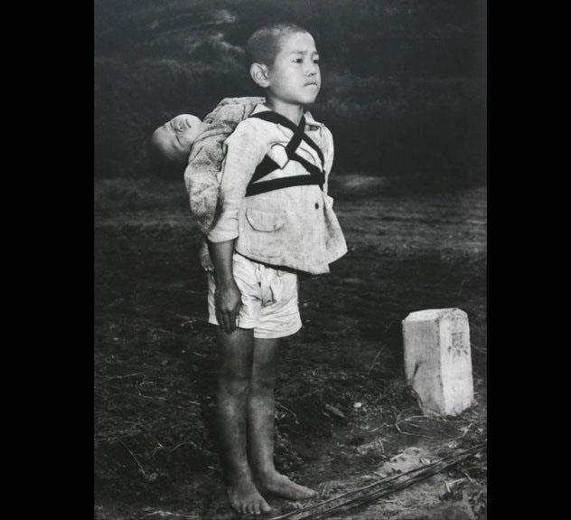 9. Los hermanos de Nagasaki: Luego de la bomba atómica, un fotógrafo americano capturó este momento tan duro como emotivo: El hermano más chico está muerto, y el más grande lo está llevando a que lo cremen.
