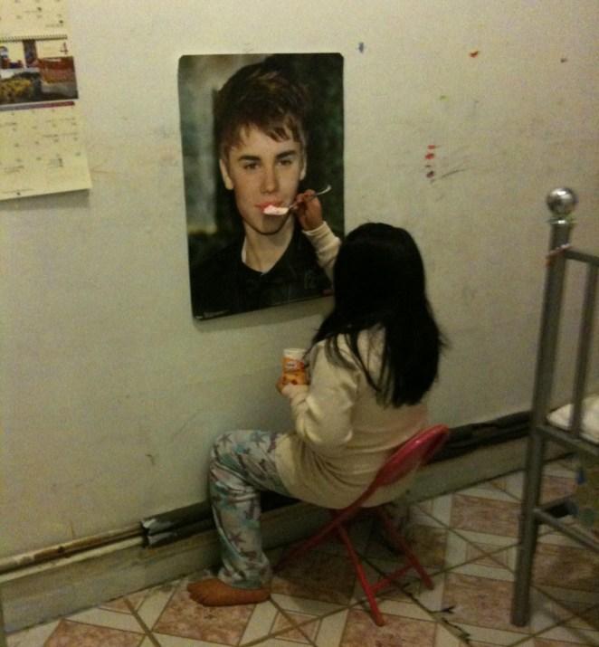 La nena que alimenta a un póster de Justin Bieber