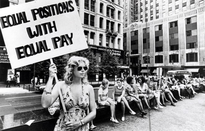 A woman stands on a corner protesting unequal pay for women in Cincinnati, circa 1971.