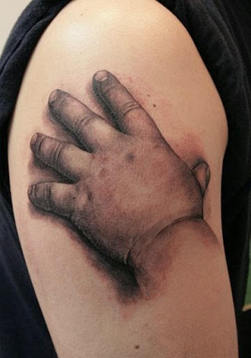 Kid's hand touching 3d tattoo designs for shoulder.