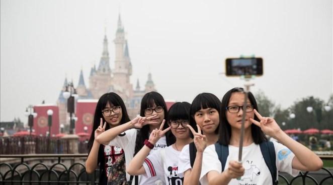 Unas visitantes al nuevo parque Disney en hacen un selfie durante la ceremonia de inauguración.