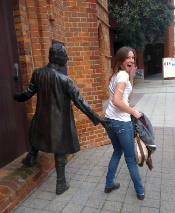 Funny People posing with statues