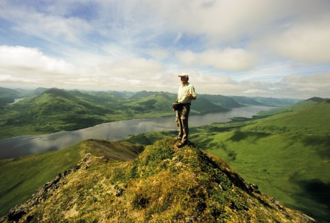 Stefan Quinth standing on top of a mountain overlooking Frazer Lake, Kodiak, Alaska