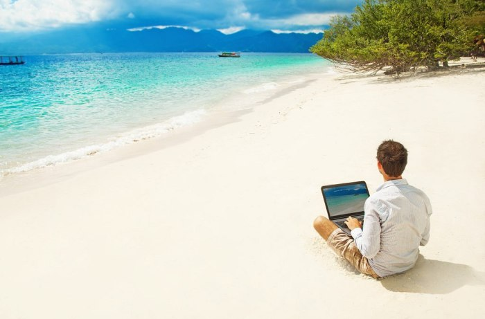 man with laptop on colorful beach of island