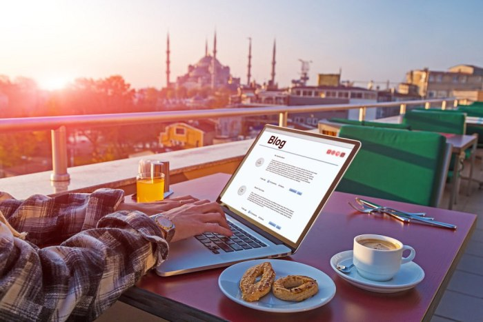 Travelling Person working on Laptop Computer at Roof Top Cafe sitting at table with Coffee Cookies and orange Juice Istanbul city Landscape on background Morning Sunlight