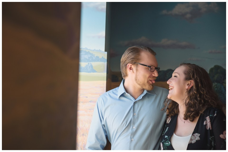 couple by window science centre engagement session regina