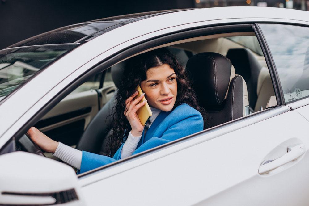 Mujer usando el teléfono móvil en el coche