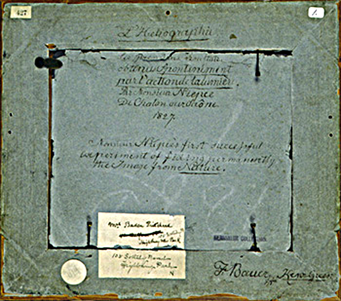 Manuscript notations and labels on the verso of Joseph Nicéphore Niépce's View from the Window at Le Gras. 1827-1963. Ink on paper backing of framed object. 25.8 x 29.0 cm.