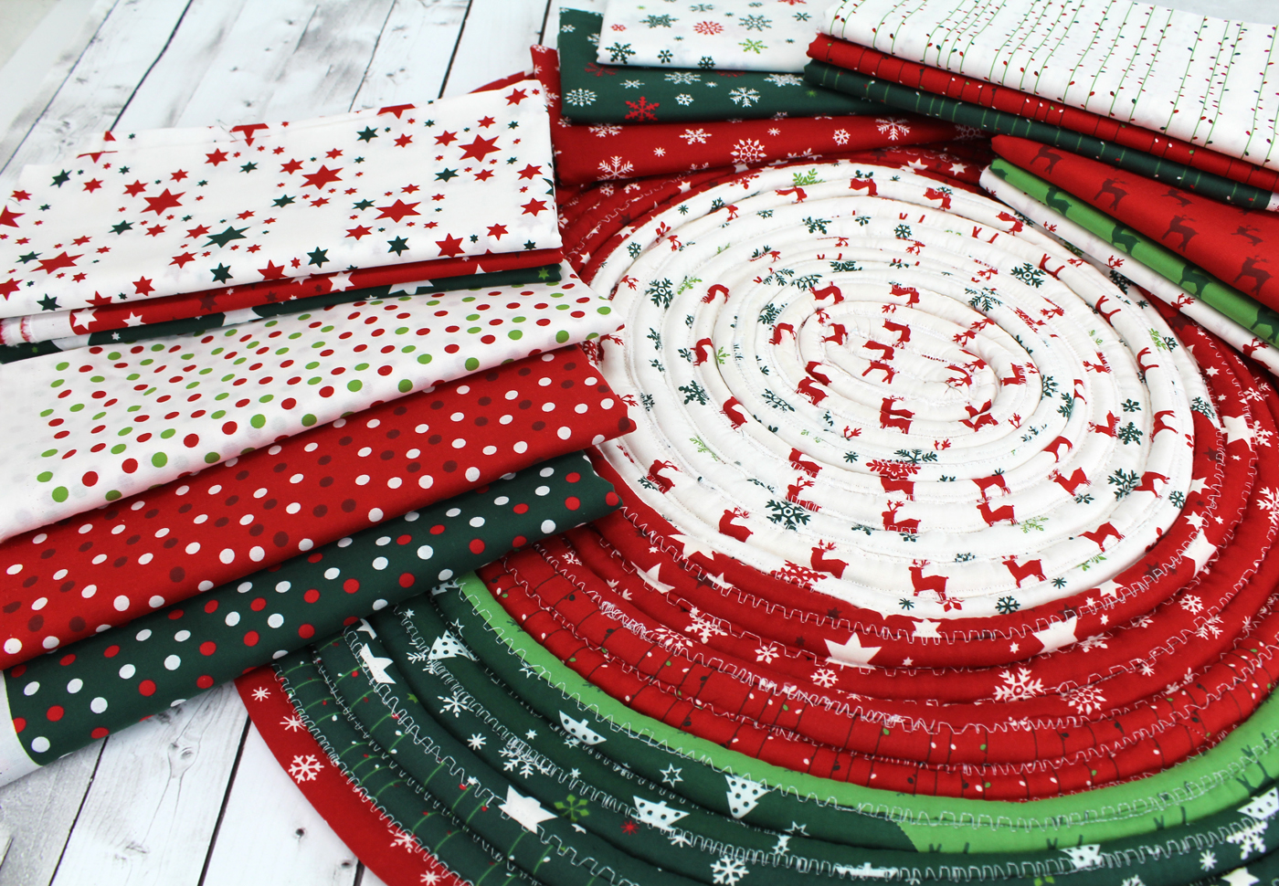 photo of the Christmas basics cotton group featuring dots, stars, snowflakes, light strings, reindeer on top of a jellyroll rug