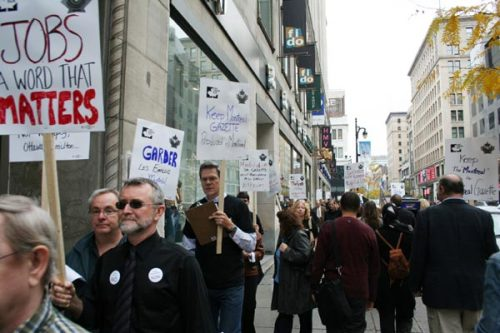 Journalists and other Gazette employees hold picket signs to attract public attention.
