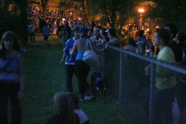 Many people gathered along the exterior fence where they could drink their beer from home