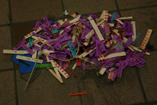 Old-style tickets and transfers from a decomissioned turnstile are swept into a pile with dust to be thrown away.
