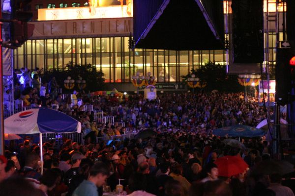 Fans at the Place des Arts plaza watch Stevie Wonder on two big screens, their view of the stage blocked by a building.