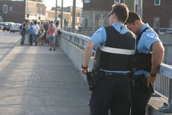 """Police officers monitor a """"flash mob"""" protest on St. Jacques St."""