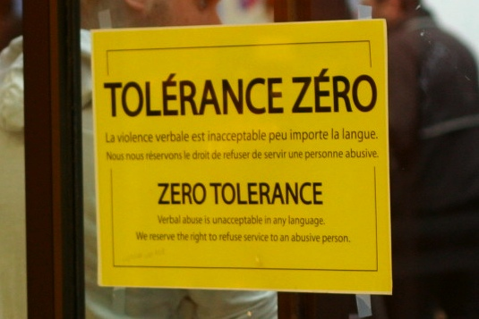 "A ""zero tolerance"" sign suggests violent outbursts from customers is a common occurrence"