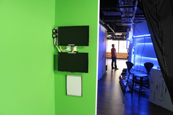 The back of the curved wall is visible from the green-screen room