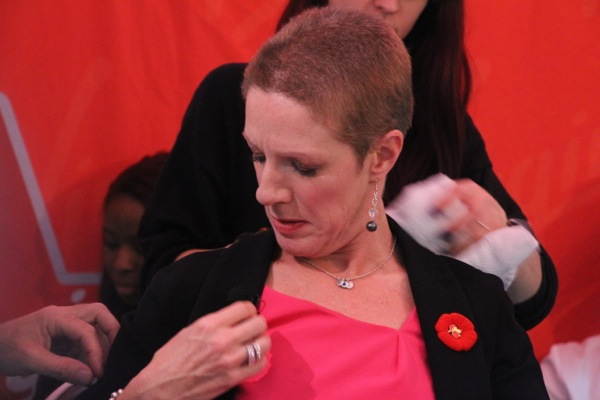 Christine Long clears some hair off of her lapel microphone.