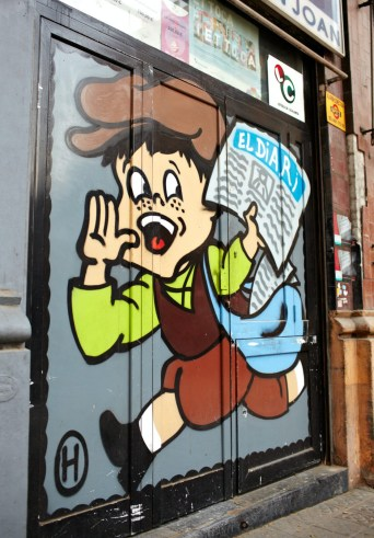 Graffiti on the wall in Barcelona. Boy runs with newspaper.