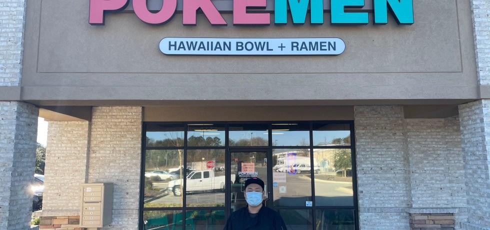 Choi standing in front of Pokémen in Opelika, AL