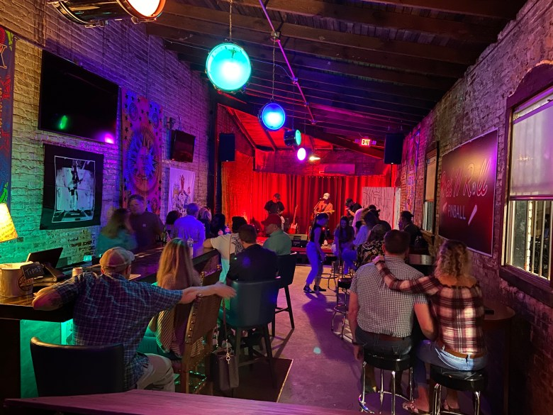 A night of live music at the Jailhouse Music Hall, depicting a live band and audience members.