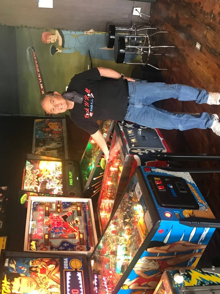 Pictured is Ernie Rains, owner of Rock N' Roll Pinball, next to a PowerPlay pinball machine