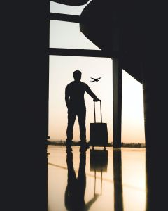 Man with suitcase standing at airport