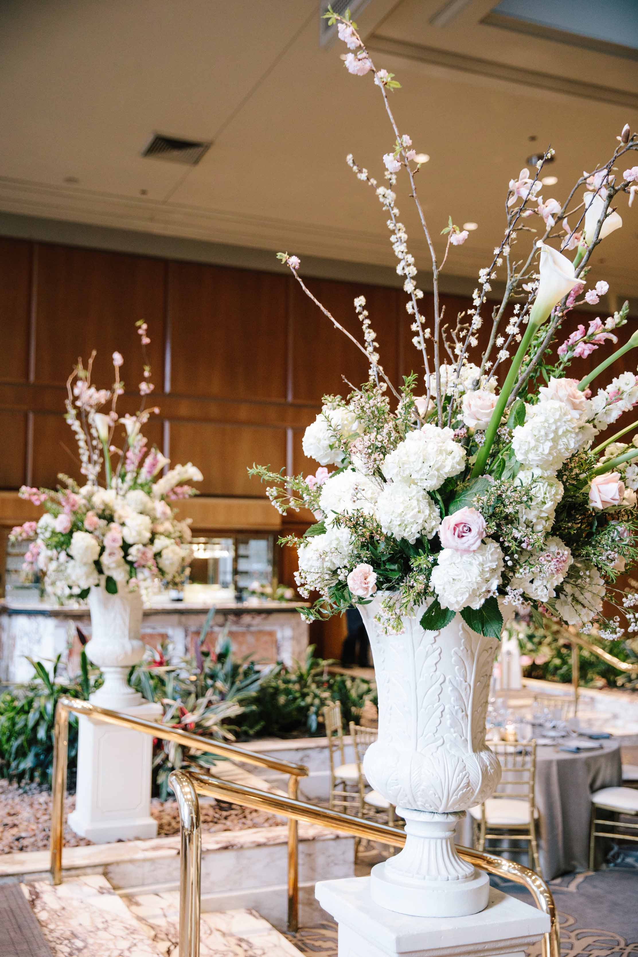 Tall white urns filled with spring garden flowers, magnolia branches, and calla lilies