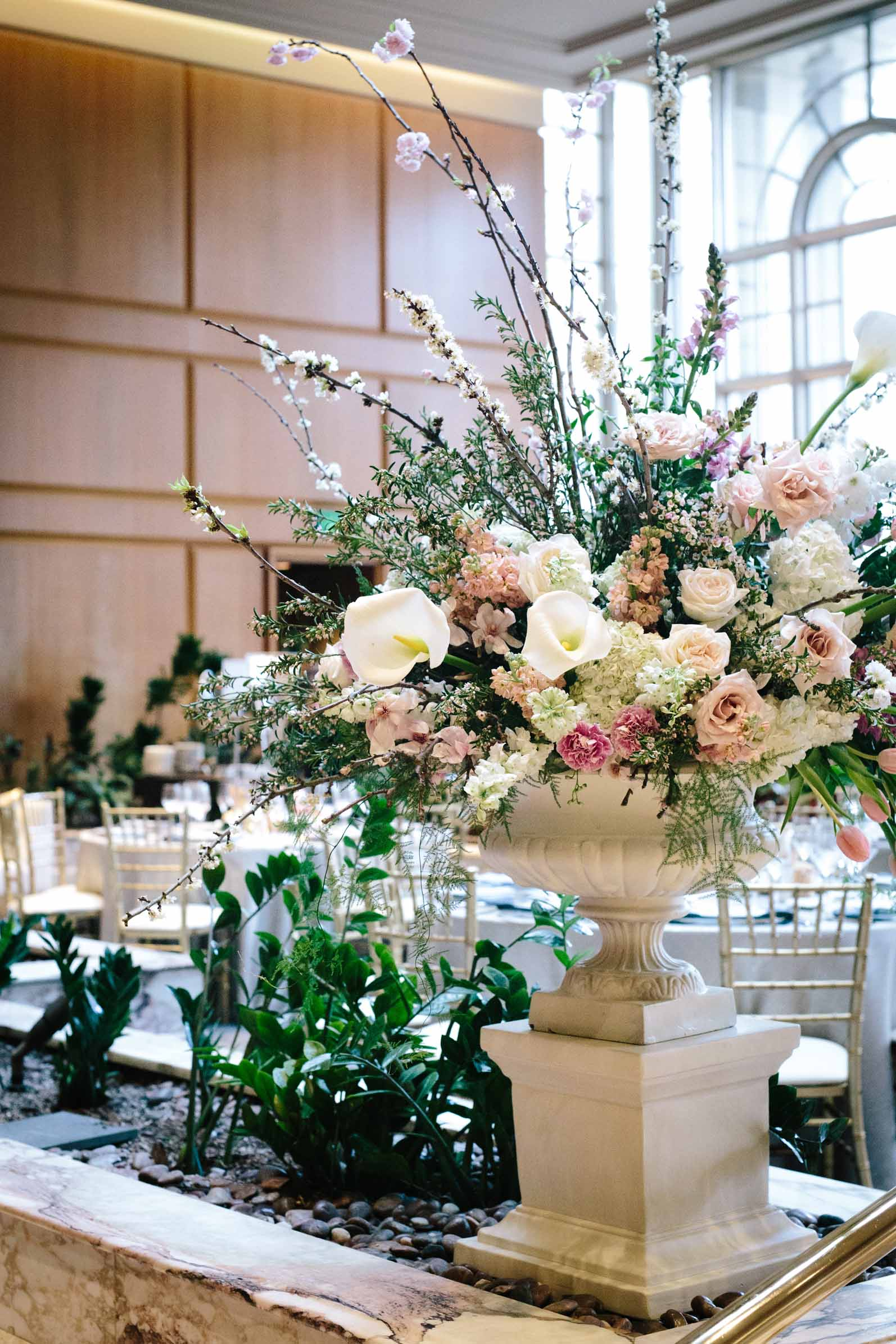 Large white urn filled with spring garden flowers in pink and white, sitting in hotel ballroom