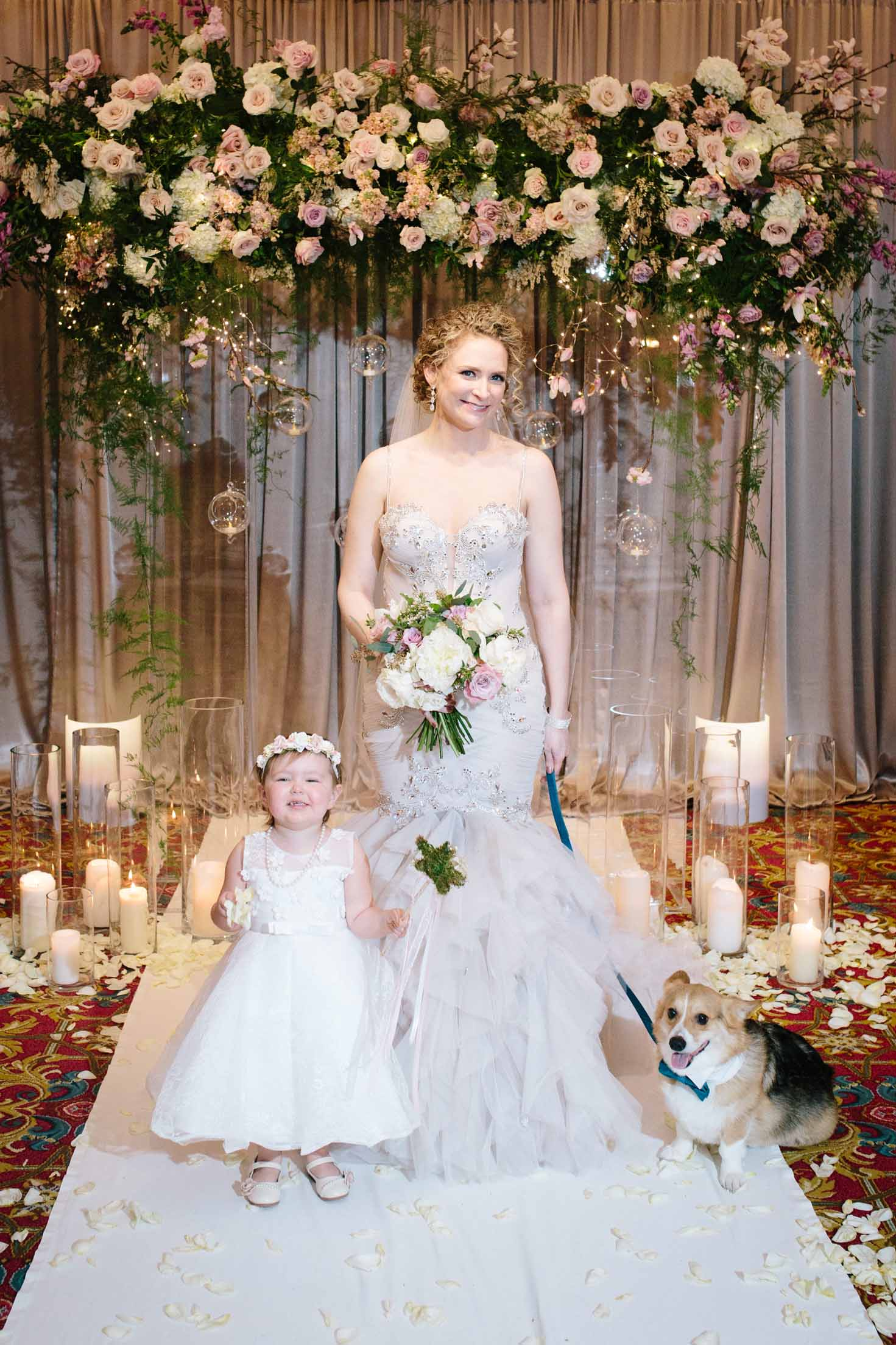 Bride standing with flower girl and dog in front of lush floral ceremony arch surrounded by candles