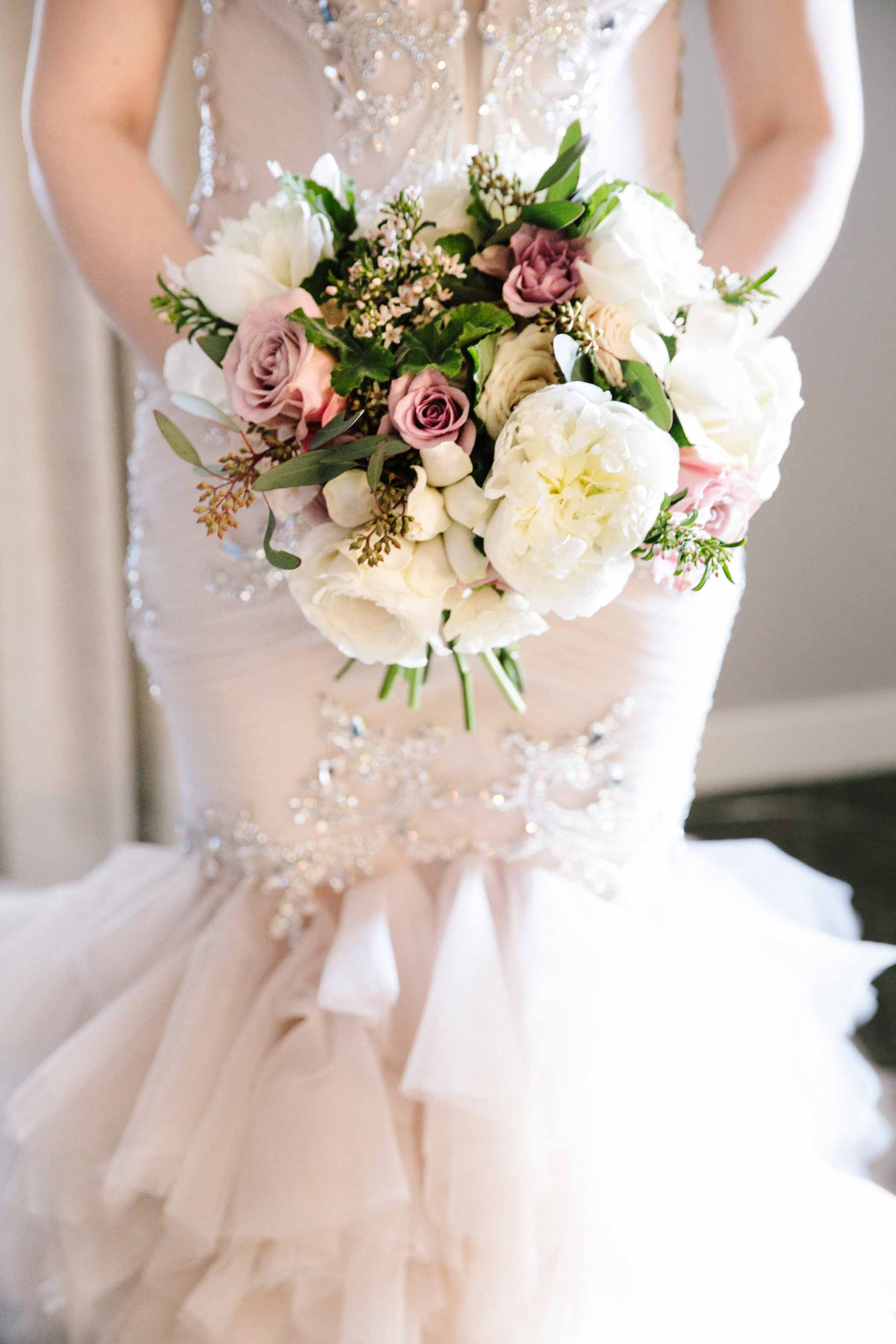 Bride in white dress holding spring garden bouquet.