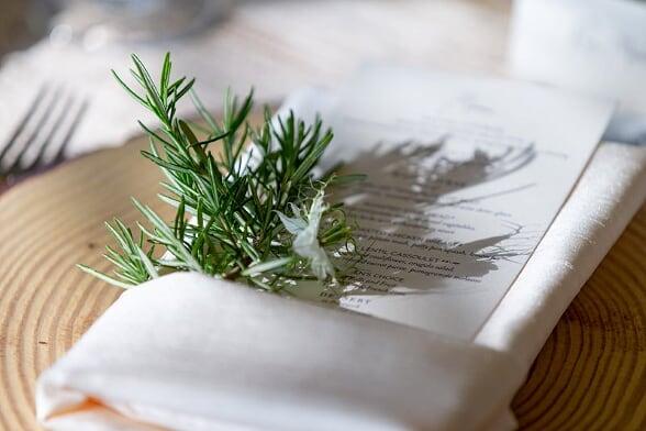 rosemary napkin greens tucked into napkin with menu card at wedding reception