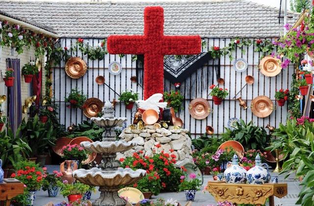 Cruz de mayo cubierta de flores en el mes de mayo - Tradición de Andalucía