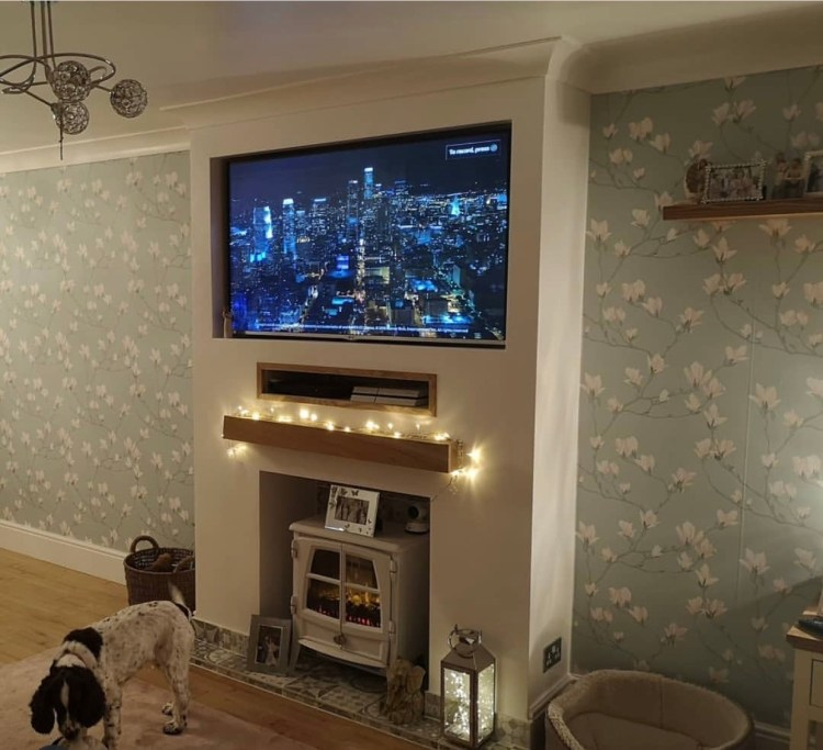 chunky oak mantel on fireplace wall with wood burner and fairy lights