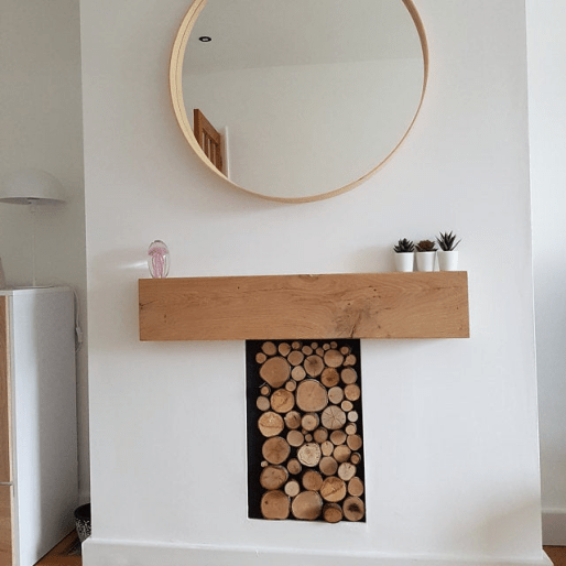 super chunky solid oak beam mantel above a wood store hearth on a white wall