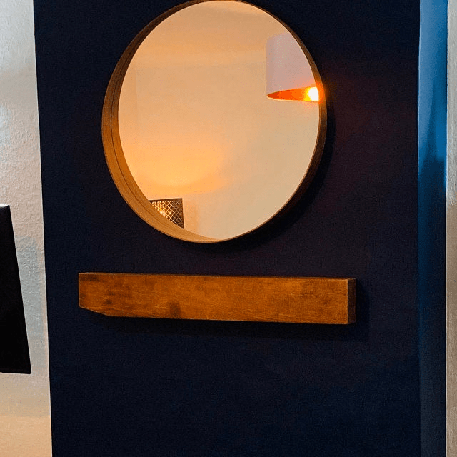 dark blue fireplace wall with large circular mirror and solid oak mantel