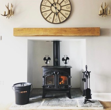 chunky solid timber mantel on white wall above black wood burner